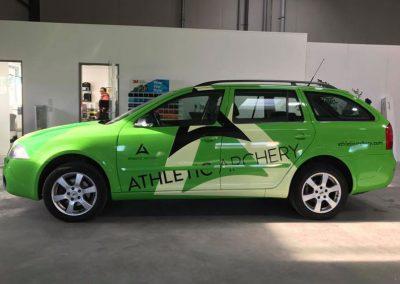 Seitenansicht einer Autobeklebung mit Werbung und Logo der Firma Athletic Apchery auf einem Skoda.
