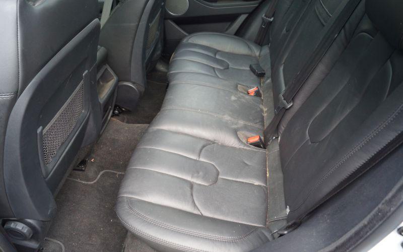 Autorücksitz aus schwarzem Leder schmutzig und stumpf vor der Autoaufbereitung.