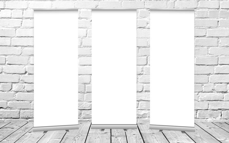 Drei Stück unbedruckte, weiße Roll up Display vor einer weißen Steinwand.