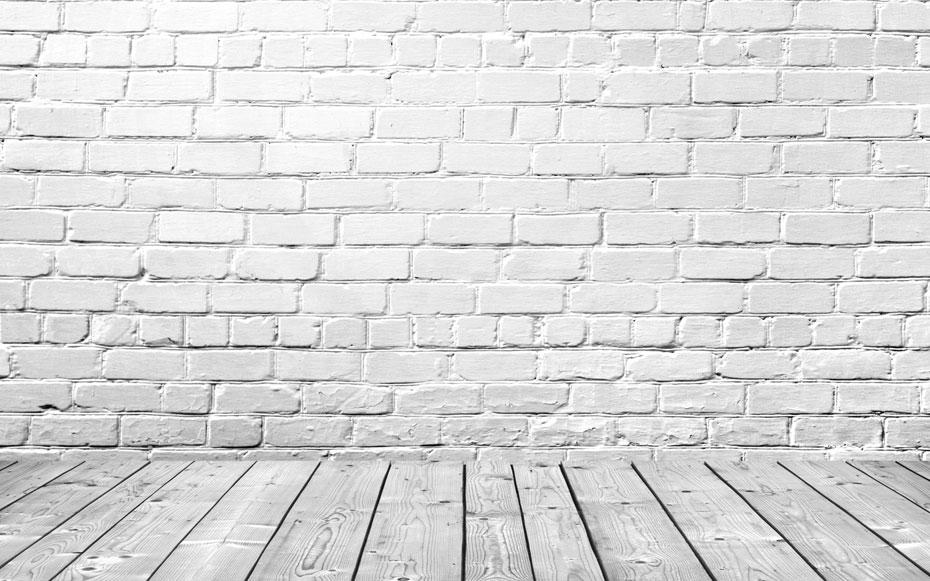 Weiße Steinwand mit weißen Bodendielen aus Holz.