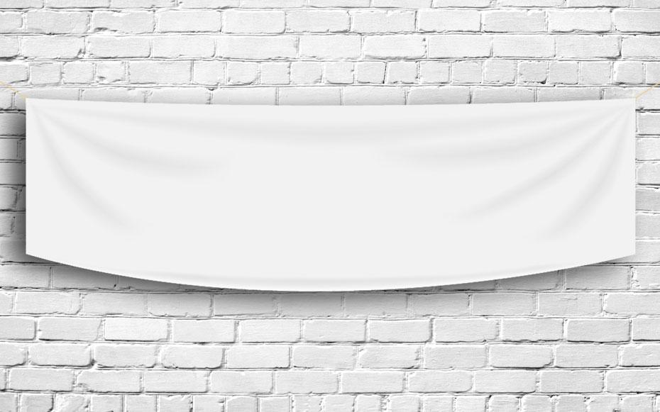 Werbebanner aus PVC unbedruck hängt an einer weißen Steinwand.