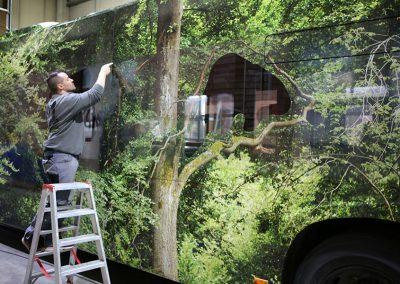 Mitarbeiter von HplusB Design schneidet Fenster aus Vollfolierung frei